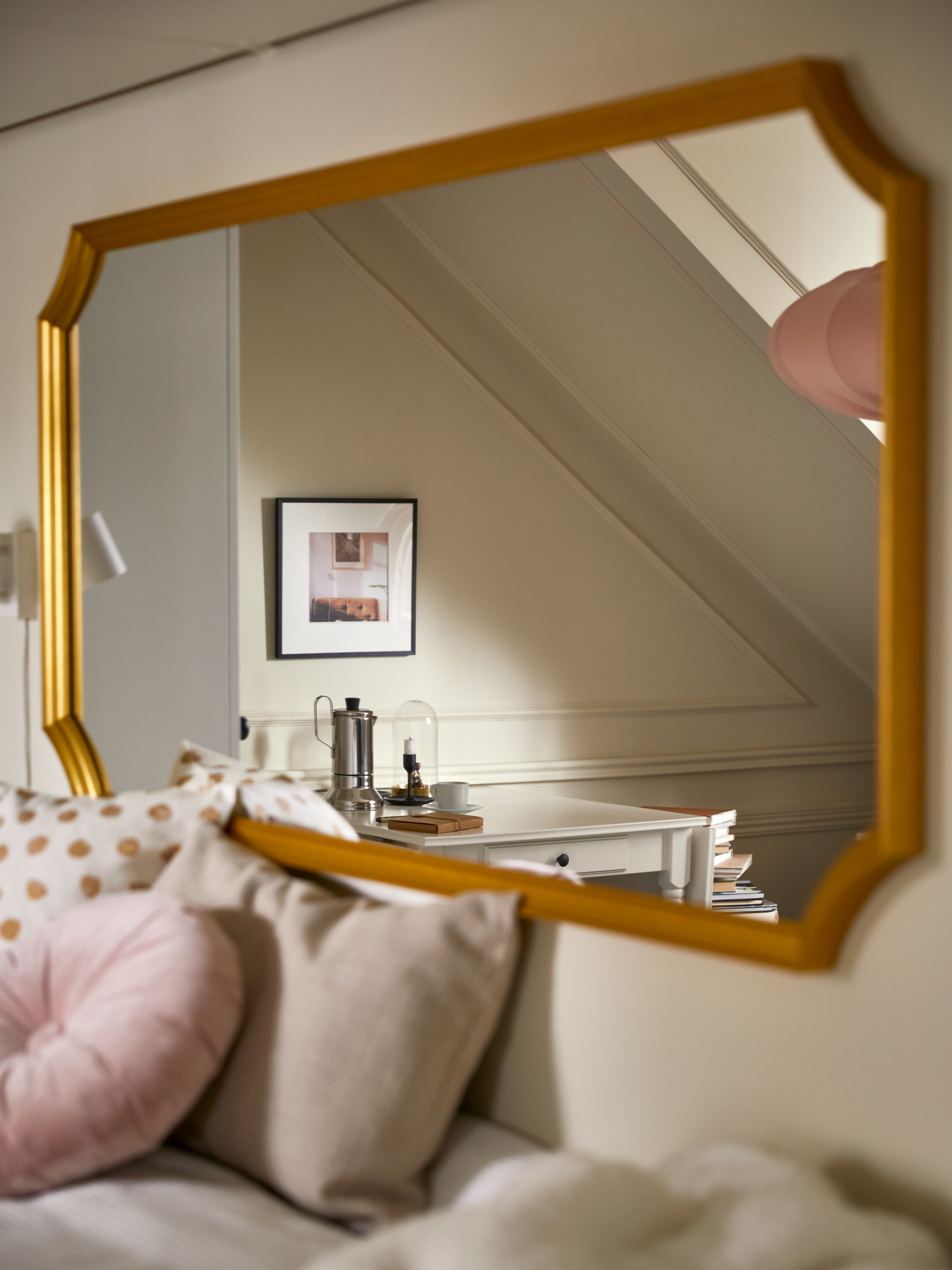 A SVANSELE gold-frame mirror at the head of a bed with cushions in various colors, plus a white table in the reflection.