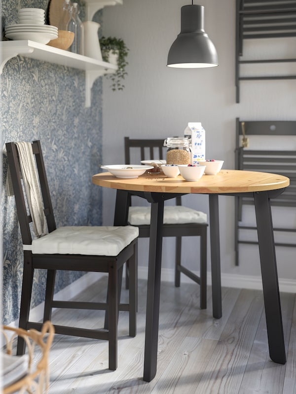 Breakfast set on a round GAMLARED table, two black STEFAN chairs, a gray pendant above and folded chairs on the wall.