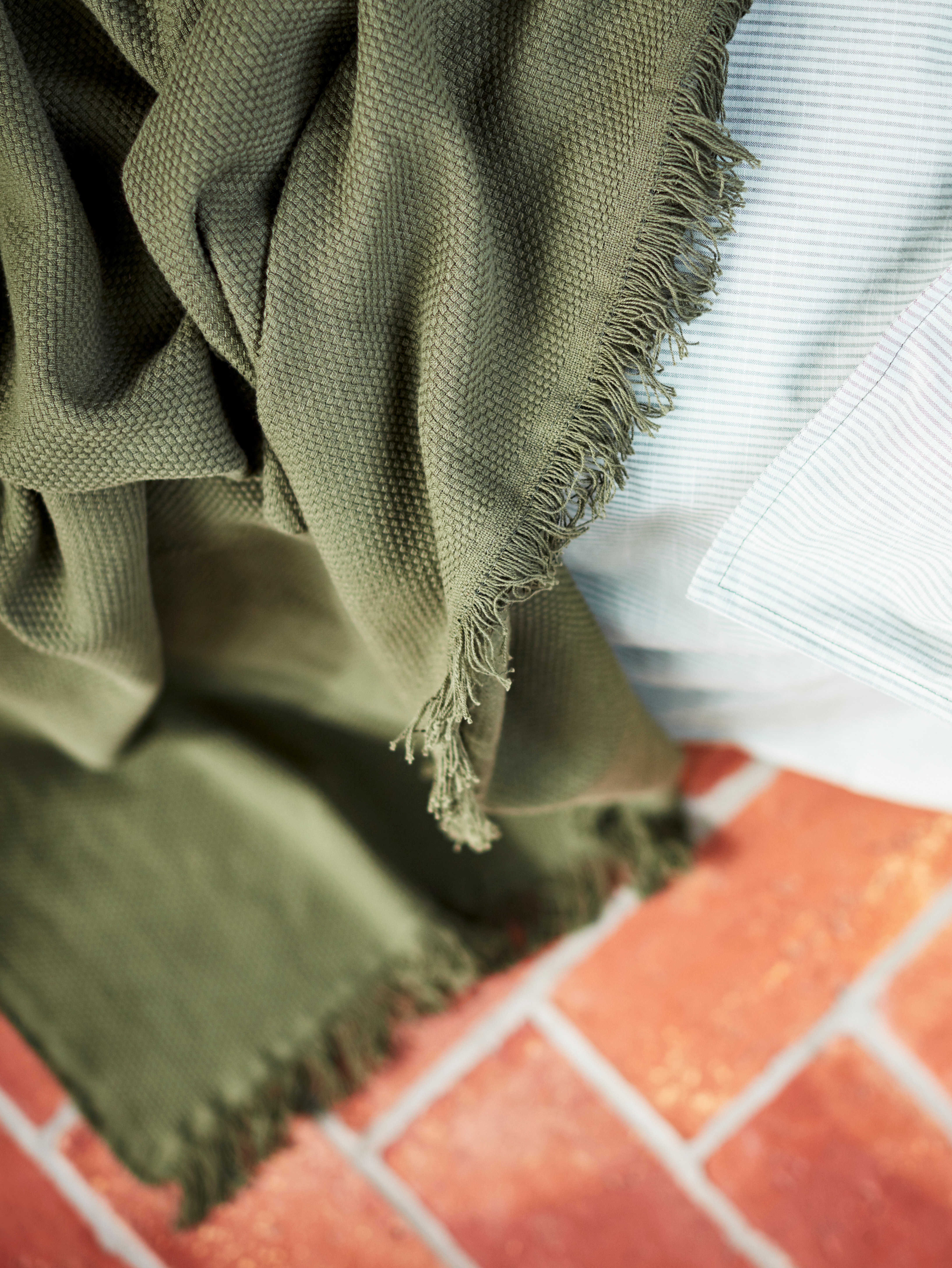 A close-up of a dark green ODDRUN throw on the edge of a bed. Its fringed edges and soft, chunky cotton weave are in focus.