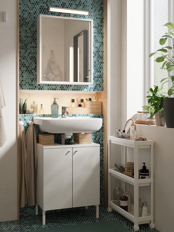 Een wit spiegelkastje en witte lavabo en een wit onderkastje naast en venster en tegen een muur met blauwe mozaiektegels.