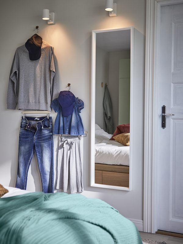 Sudut bersalin pakaian yang mempunyai cermin panjang, dua lampu dinding dan cangkuk dengan pakaian dan topi pada penyangkut.