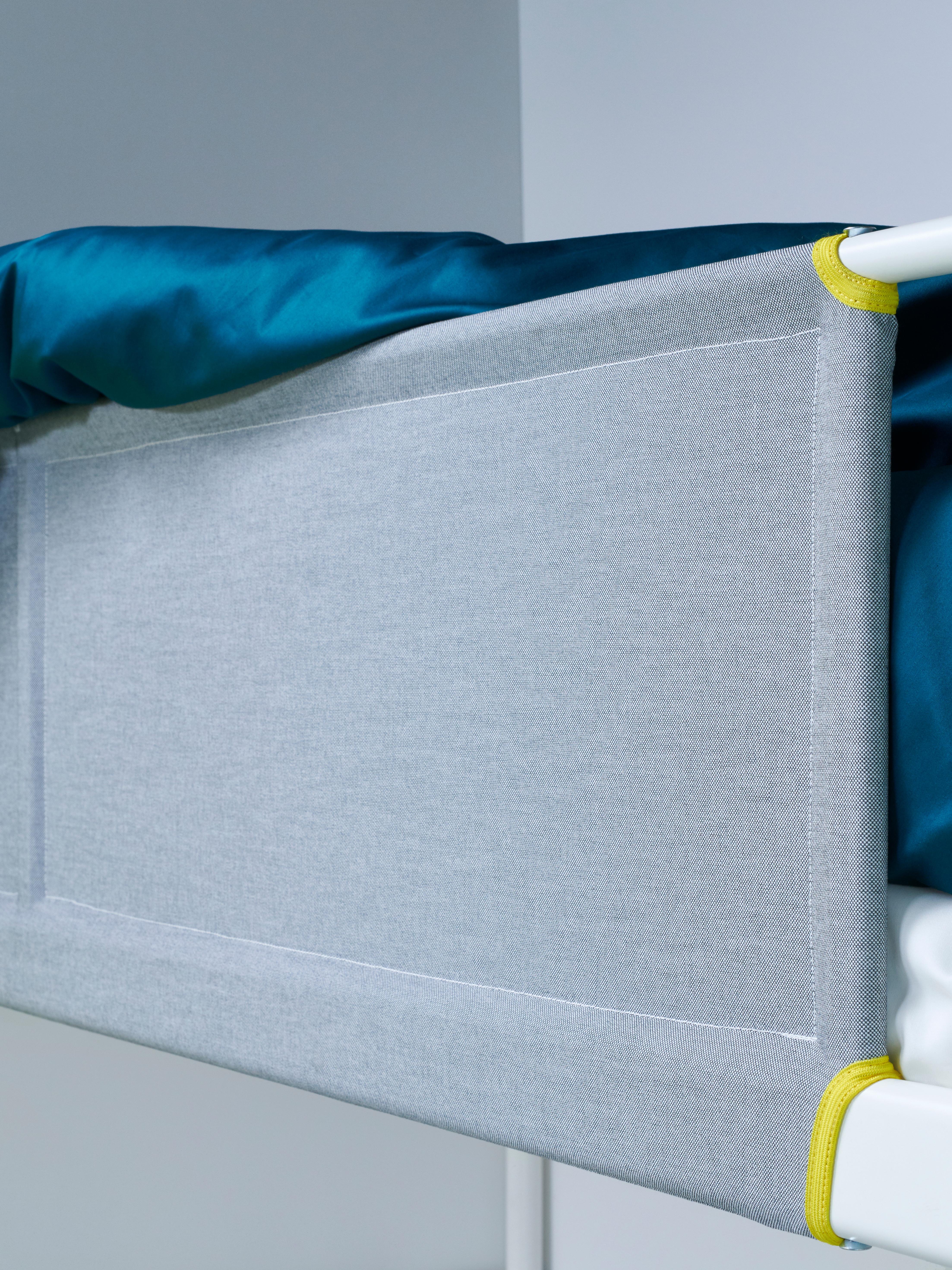 Prikaz sive tekstilne zaštitne ograde za krevet na kat.