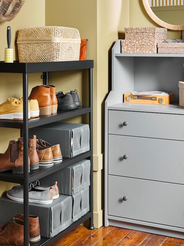 In een hoek in de gang staan een zwarte KORNSJÖ stellingkast met schoenen en schoenendozen en een grijze HAUGA ladekast.