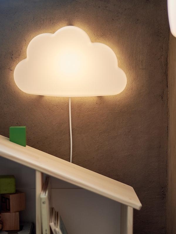 Vegglampe formet som en sky henger på en mørkebrun vegg over en vegghylle av tre for barn.