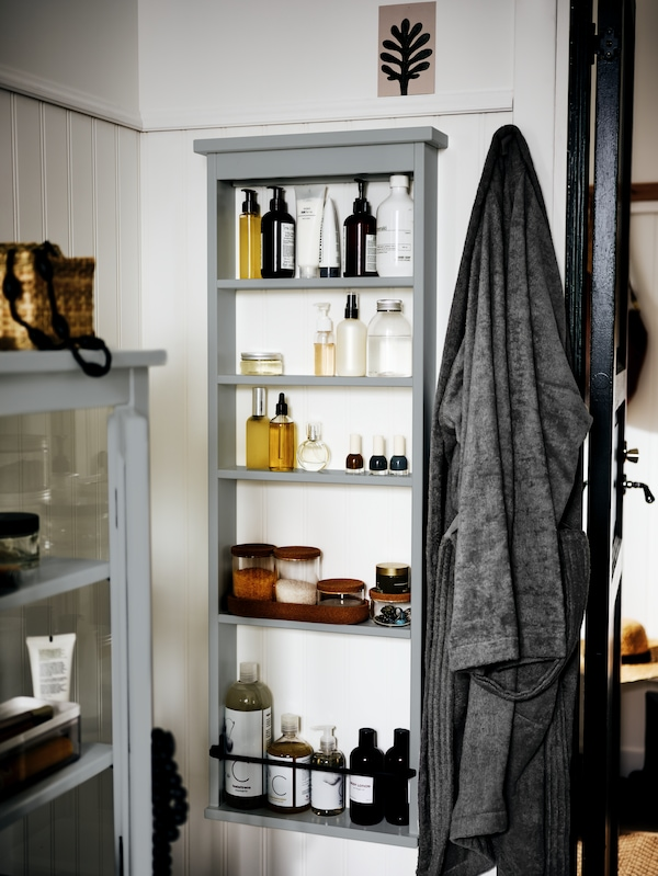 The corner of a white bathroom with a HEMNES wall shelf on one wall. Toiletries and bathroom accessories are on the shelves.