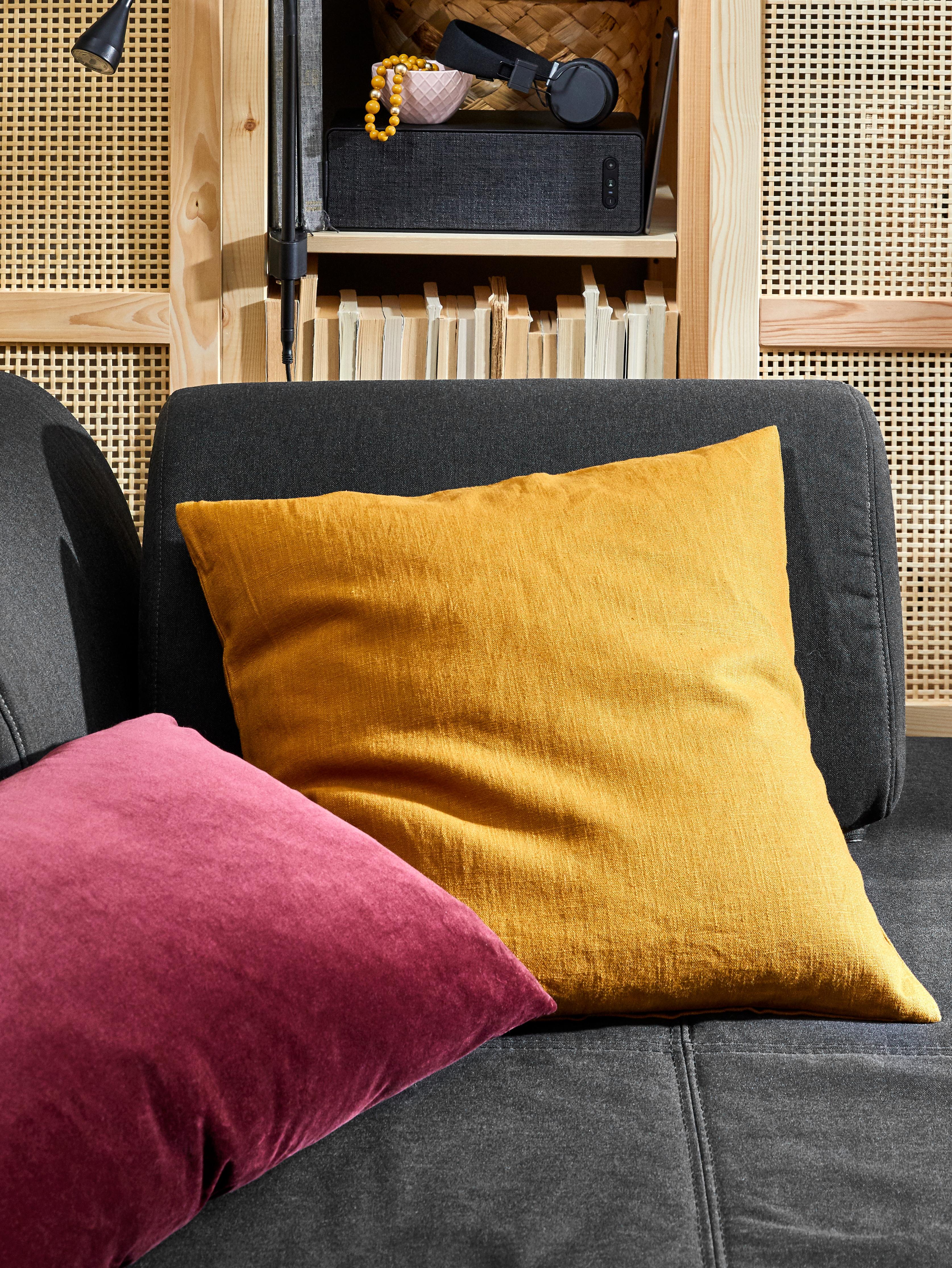 FLOTTEBO sofa oheko izkinan kuxinak ditu VIDGIS estalkiekin urre marroiarekin eta SANELA arrosa ilunarekin.
