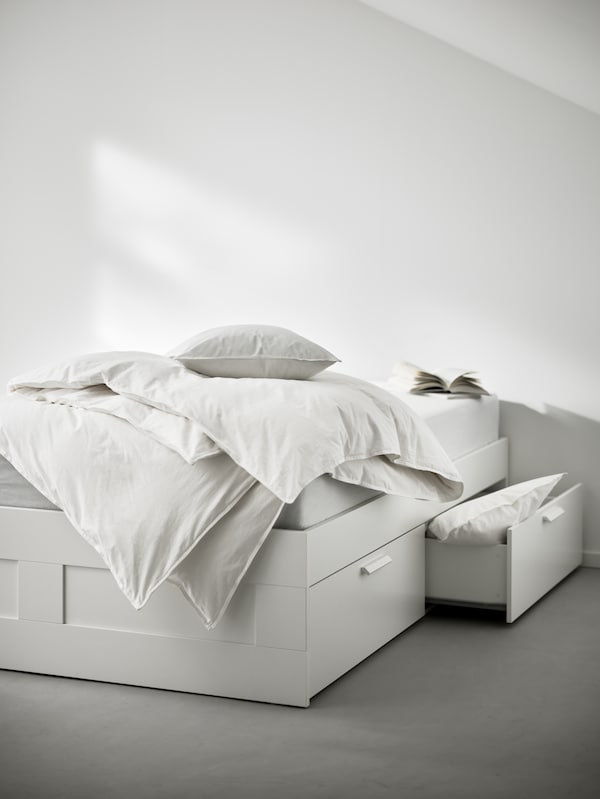 One side of a white BRIMNES bed frame with storage, with ruffled bed linen and books on top, and one strorage drawer open.