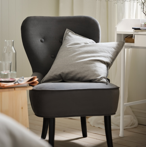 Part of a bedroom with a dark-grey REMSTA armchair, contrasting against an otherwise light colour scheme.