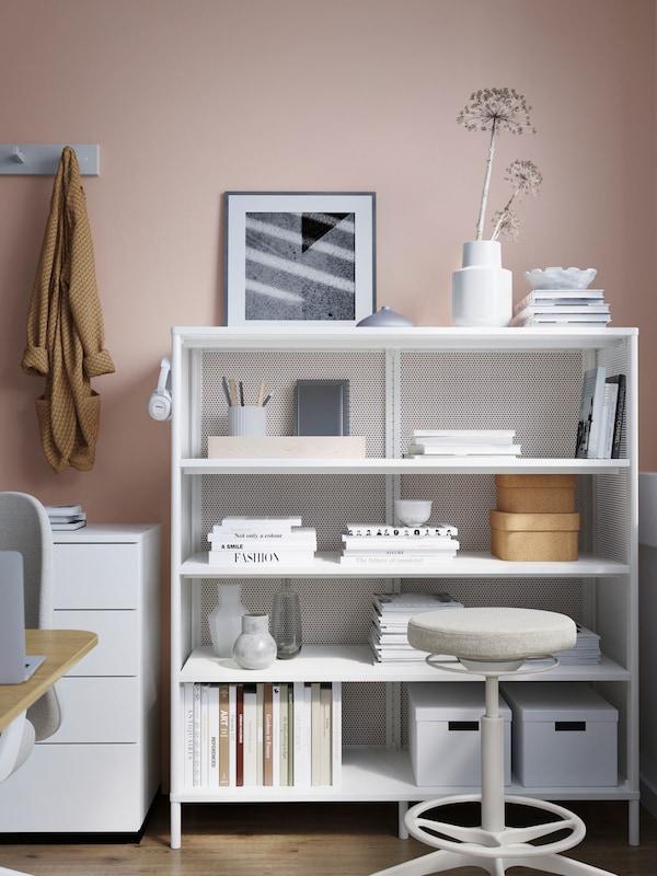 Weiße Aufbewahrungselemente, eines mit Schubladen, das andere ein Regal mit unterschiedlichen Utensilien. Davor steht ein Hocker.