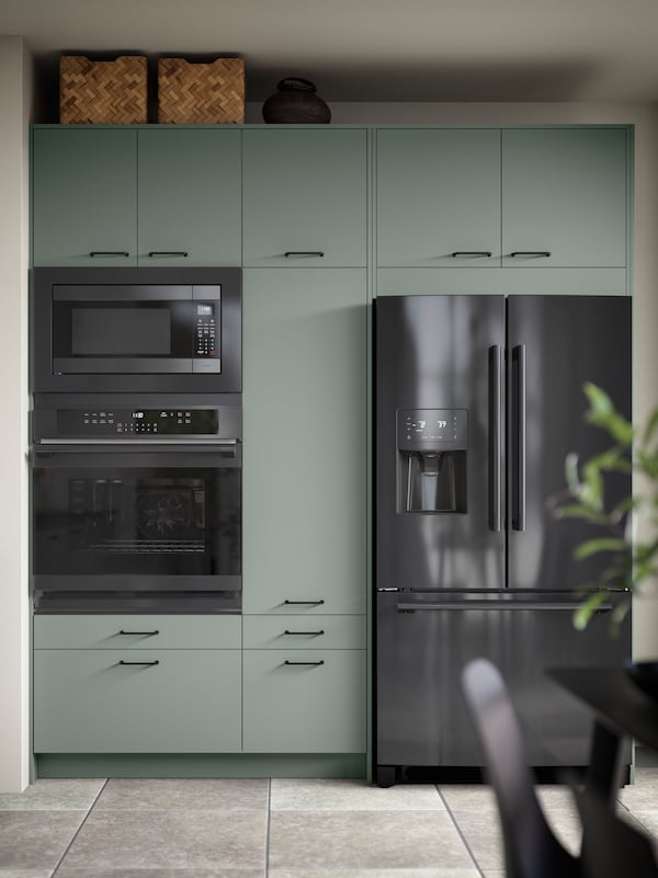 A BODARP green kitchen with black stainless steel appliances