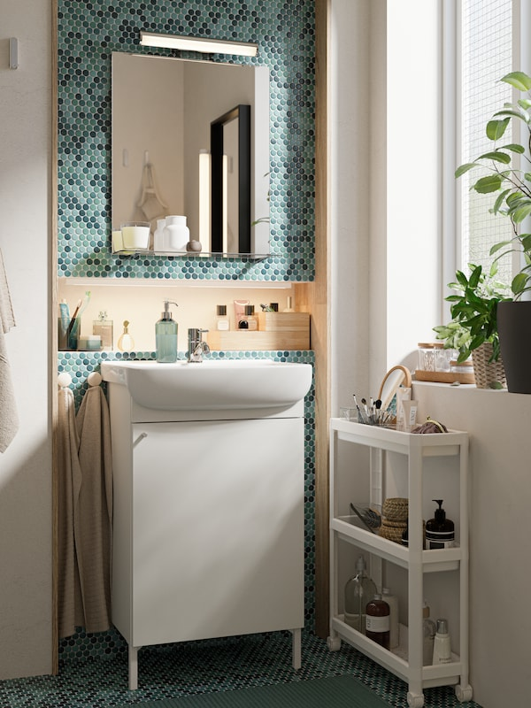A green-tiled bathroom, vanity cabinet, mirror with shelf, white cart and plants on a windowsill.