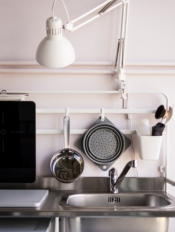 A work lamp clamped to a kitchen's frame. Utensils, a portable induction hob and washing up accessories hang on hooks.