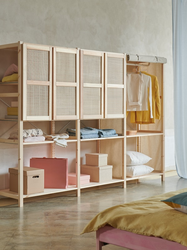 An IVAR combination in natural-coloured pine wood with three sections and bamboo doors, being used as a wardrobe.