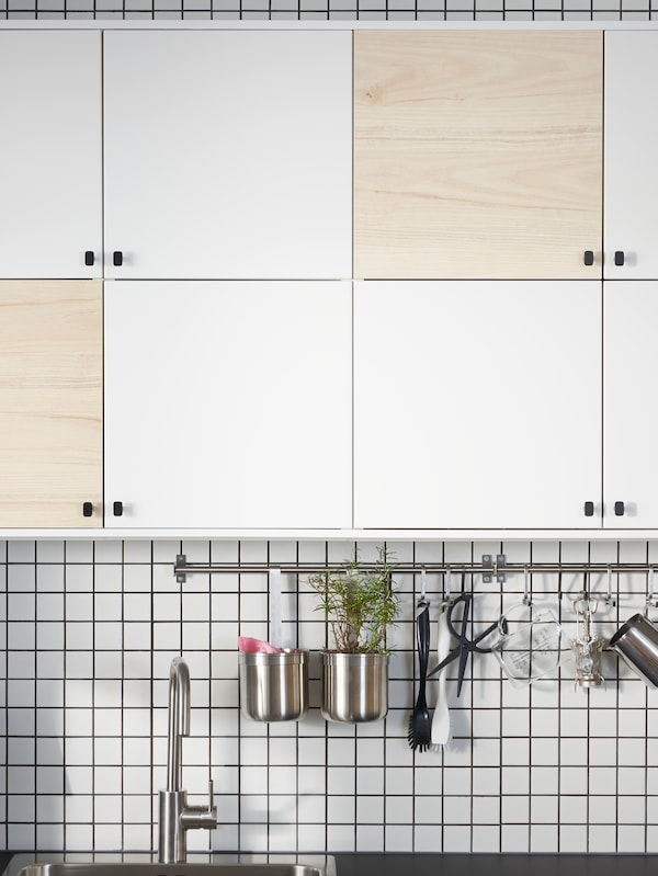 Cabinets on a kitchen wall with six doors in white and two doors in a light ash effect to make a pattern.