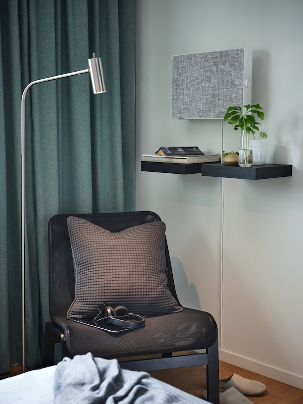 En sort lænestol, en forniklet gulv- og læselampe, sortbrune væghylder og en hvid luftrenser.
