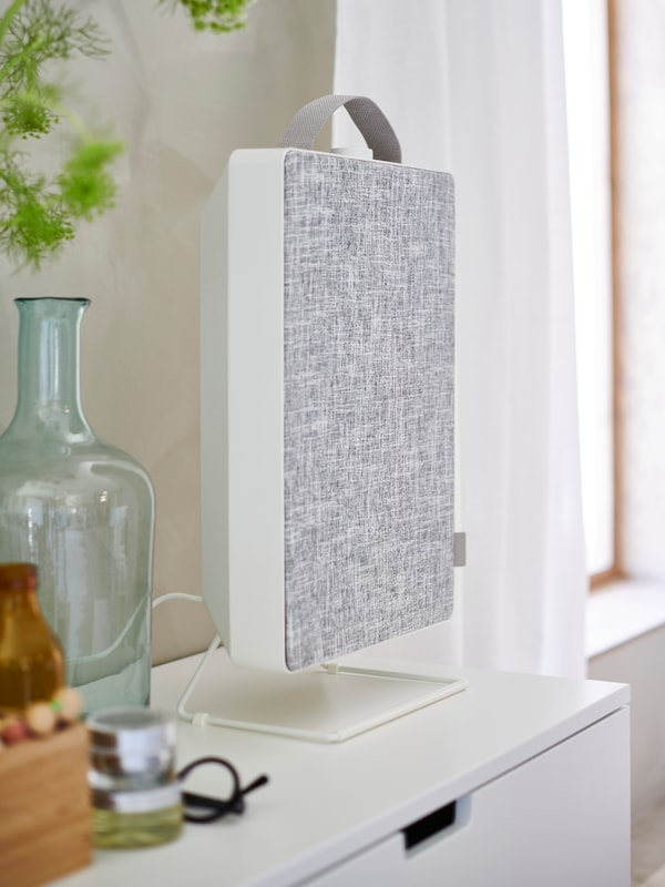 A close-up of a white FÖRNUFTIG air purifier placed on top of a white chest of drawers, next to a glass carafe.