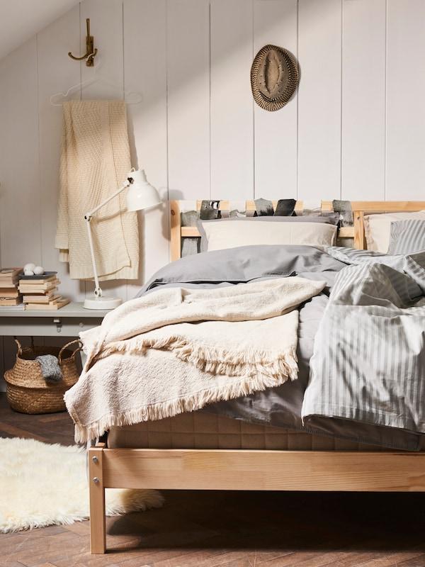 Une chambre confortable dans des tons et des matériaux terreux. Le lit en bois est recouvert de plusieurs couches de textiles. À l'arrière, les panneaux de bois blanc sont visibles.