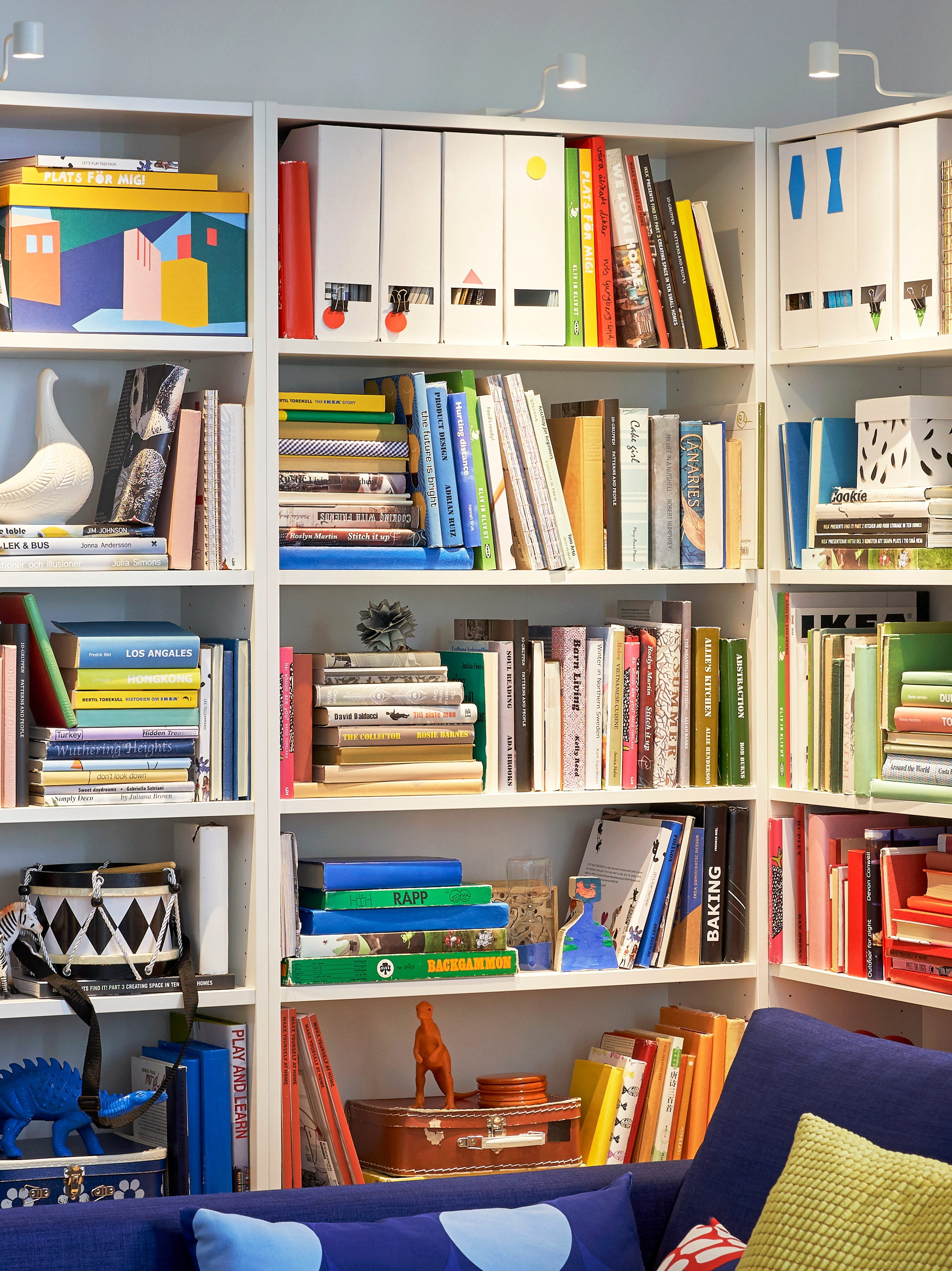 Three white BILLY bookcases are on a corner wall in a room and filled with colourful books, toys and decorative objects.