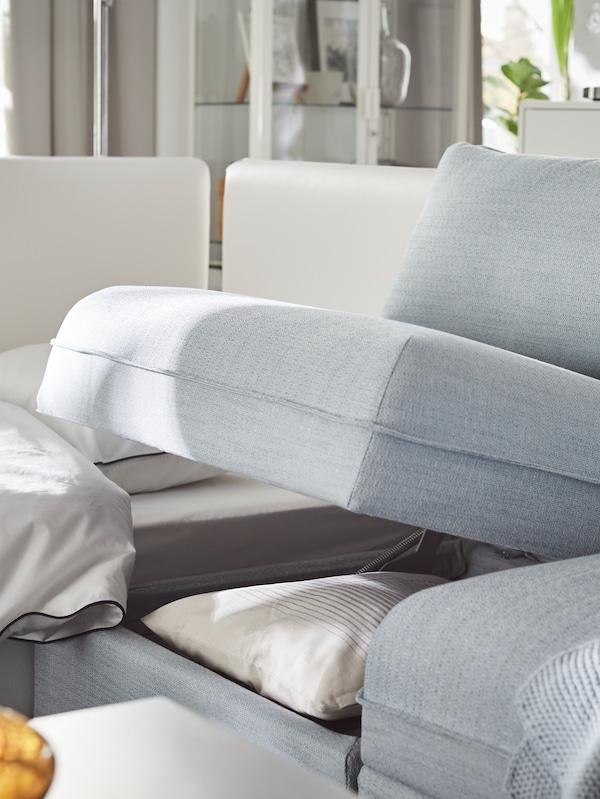 Canapeaua modulară VALLENTUNA, albastră, de la IKEA, cu spațiu de depozitare deschis, lăsând să se vadă lenjerii de pat și perne.