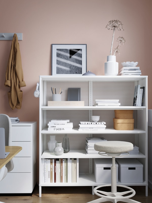 White open storage with decorative items on top, the shelves full of books, boxes, files and diverse pots, and a stool.