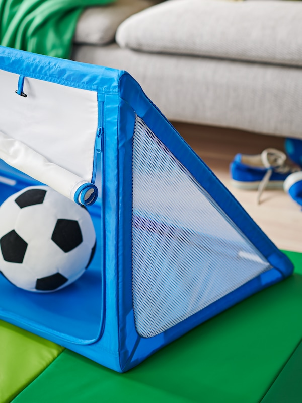 A SPORTSLIG toy goal with storage, its zippered mesh front halfway down, with a black-and-white SPARKA toy football in it.