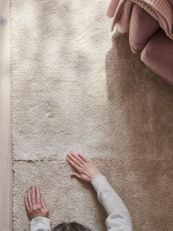 A STOENSE low pile rug in off-white, seen from above in a living room, with a person feeling the rug's soft, dense surface.