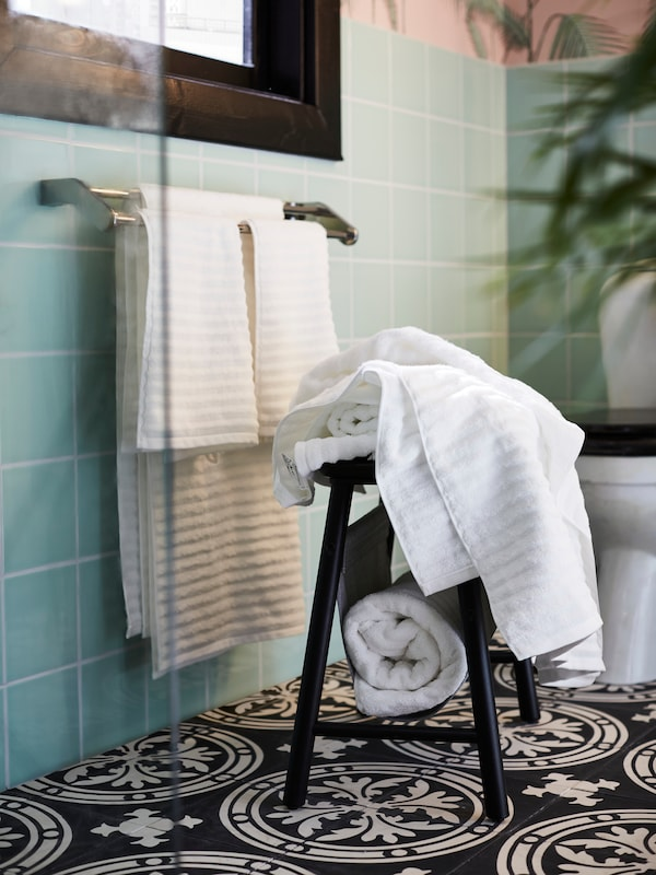 White FLODALEN hand and bath towels on a towel rail on a light green tiled wall. More towels are on a black stool in front.