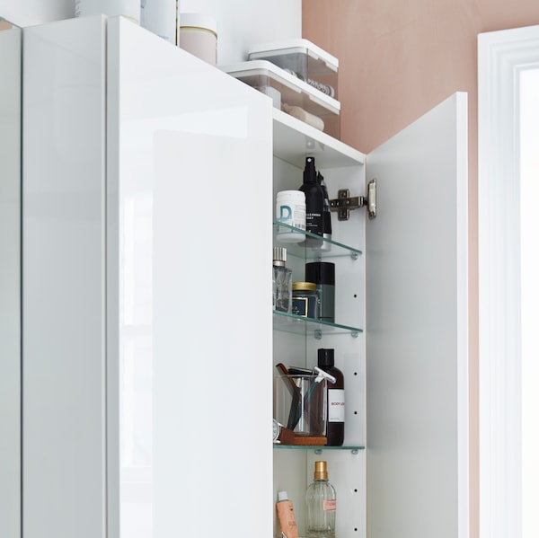 A white wall cabinet with a half-open door where various bathroom products are stored inside and on top.