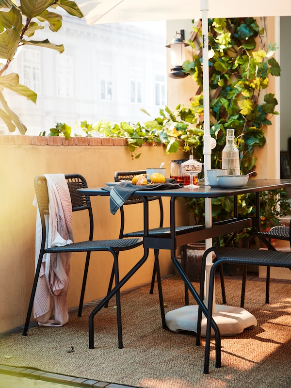 VIHOLMEN outdoor chairs and a VIHOLMEN outdoor table with breakfast on it stand outside on a rug under a parasol.