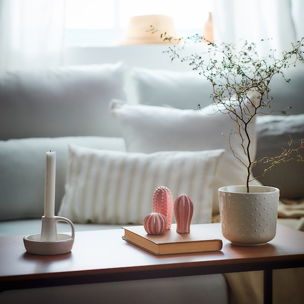 Several decorative items including a white ceramic vase, pink cactus, and white candlestick are placed on a coffee table, with a white sofa and cushions in the background.
