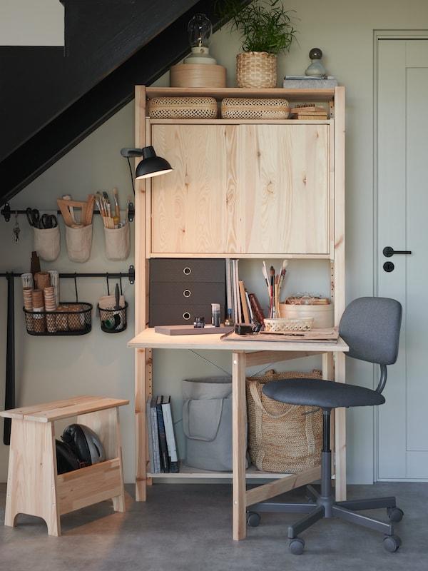 Un rangement IVAR avec table pliante sous les escaliers, et une chaise de bureau placée à côté. Des barres-supports auxquelles sont suspendus des contenants remplis d'outils.