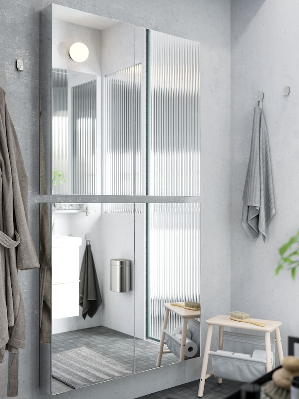 Two GODMORGON mirror cabinets with doors are placed on top of each other on a light grey bathroom wall.