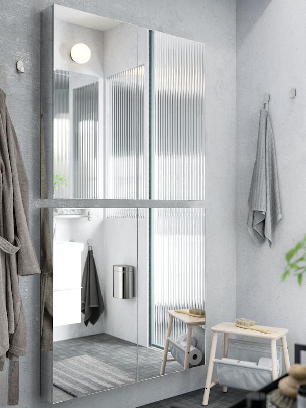 Två GODMORGON spegelskåp med dörrar har placerats bredvid och ovanpå varandra på en ljusgrå badrumsvägg.