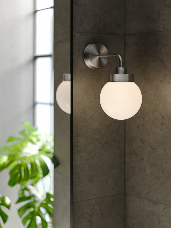 Une applique FRIHULT en acier inoxydable allumée, fixée sur un mur dans un coin à côté d'un miroir LINDBYN noir.