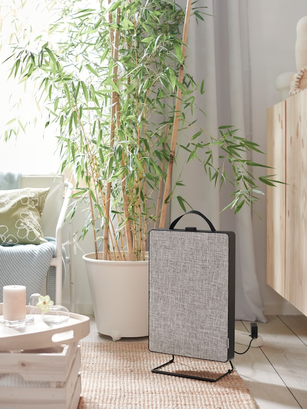 Living room with a jute rug, a FÖRNUFTIG air purifier, a GUNRID air purifying curtain and a tray with a scented block candle.