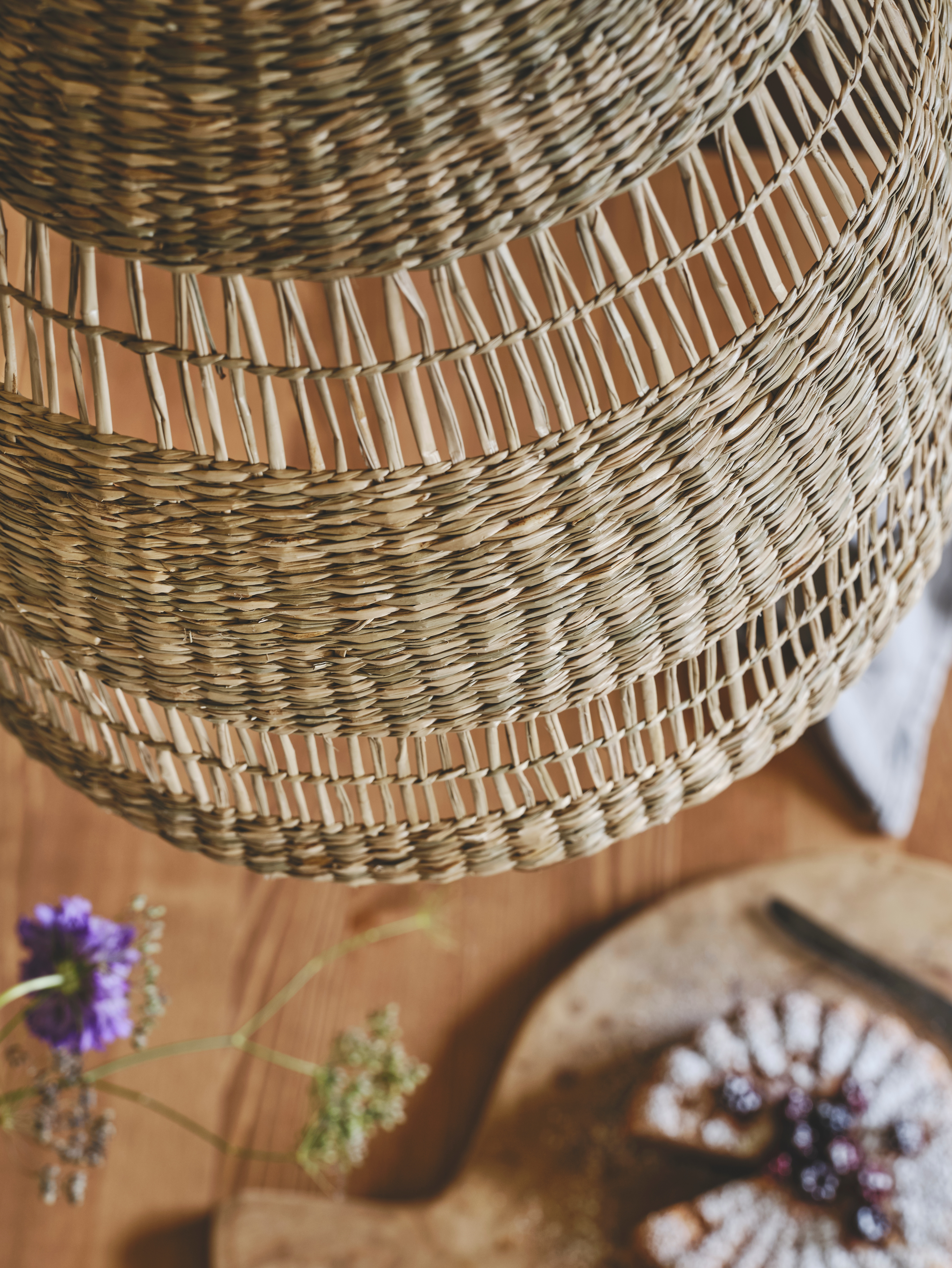 Close-up shot of natural hand-woven lampshade made from seagrass hanging above a wood table in the dining room.