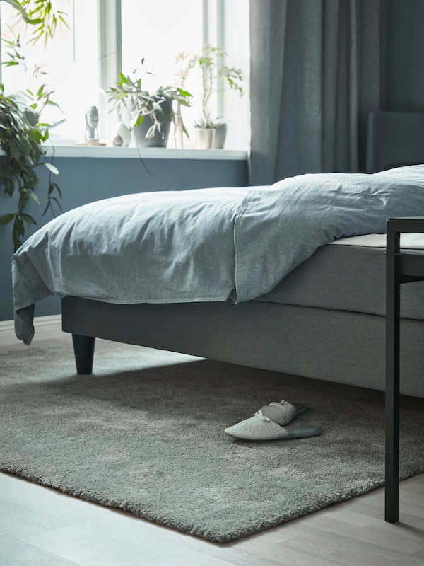 Harmaansävyisessä huoneessa harmaa sänky, jonka alla harmaa lämmin matto. Ikkunasta tulvii luonnonvaloa ja ikkunalaudalla on kasveja.