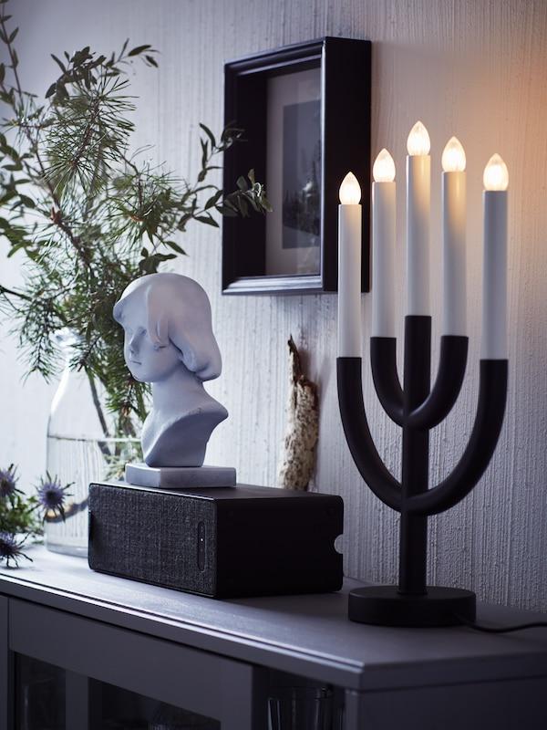 블랙 SYMFONISK 쉼포니스크 WiFi 스피커가 블랙 STRÅLA 스트롤라 LED촛대5등과 거실장 위에 놓인 다른 장식품 옆에 있는 모습.