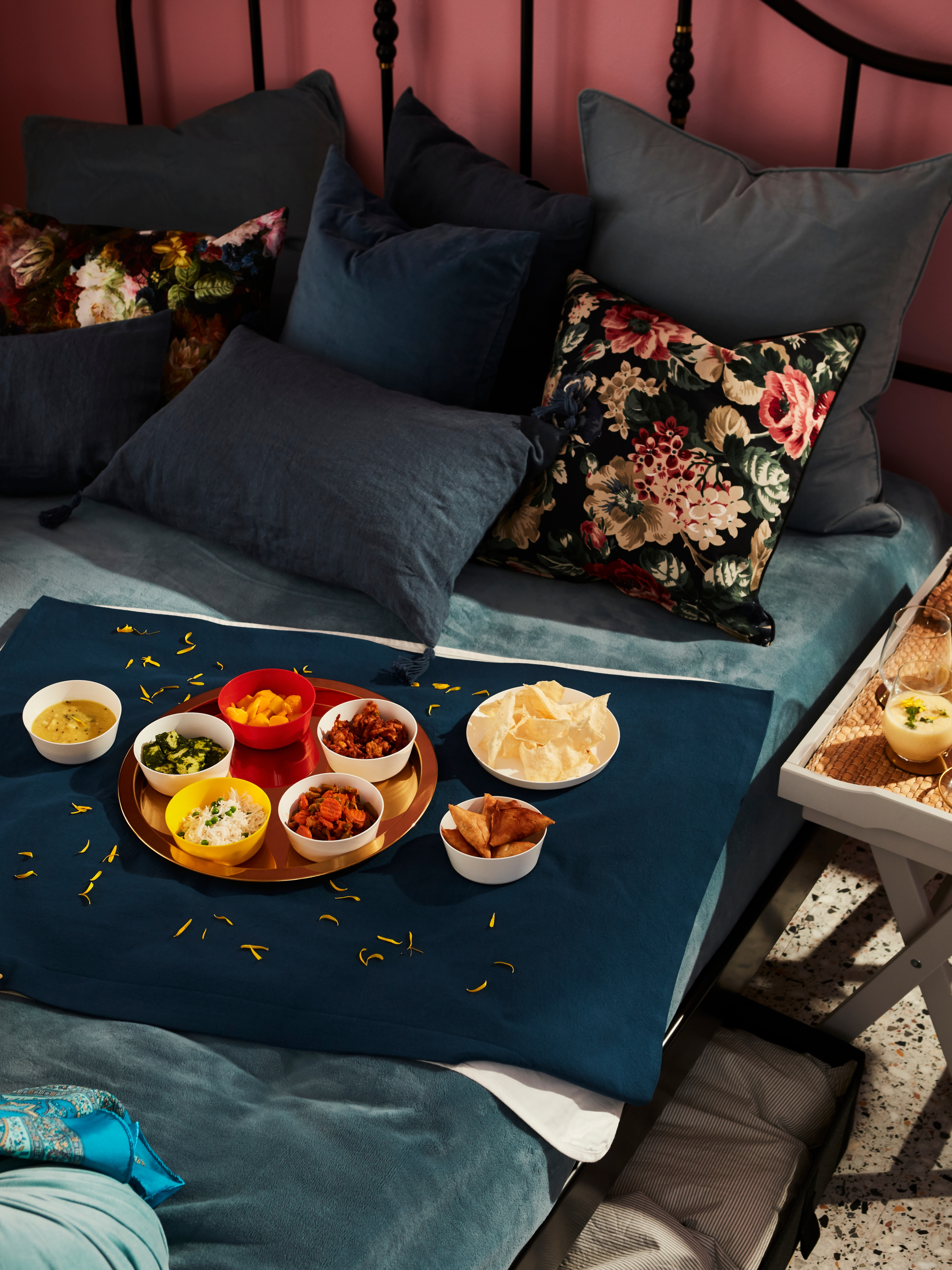 A made bed has a thin cushion on it like a table. A round, brass-coloured GLATTIS tray with bowls of food is on the cushion.