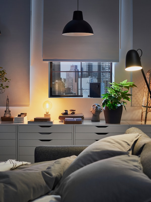VIMLE bäddsoffa utbäddad till säng lyses upp av en SKURUP golv-/läslampa, med fyra vita ALEX hurtsar med lådor i bakgrunden.