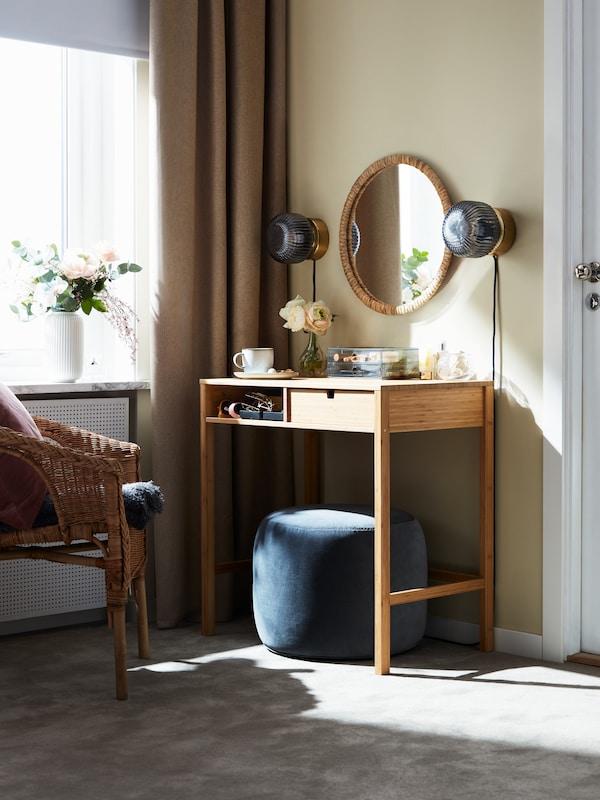 une coiffeuse dans une chambre avec un miroir rond placé au dessus et deux appliques au mur