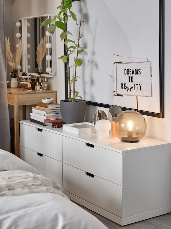 Two white NORDLI chests of drawers stand against a wall. Table lamps, books and decorative items stand on top of them.