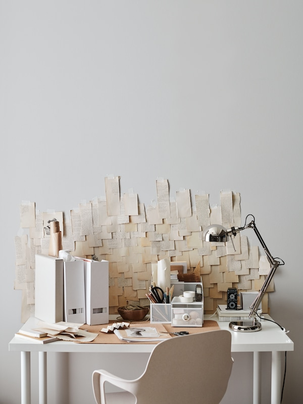 A white workspace with magazine files, a DRÖNJÖNS organizer and a FORSÅ work lamp. The wall behind is covered with notes.