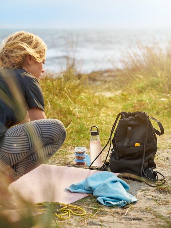 une femme sportive allongée sur la plage, portant un sac de sport Varldens et une serviette Kornan