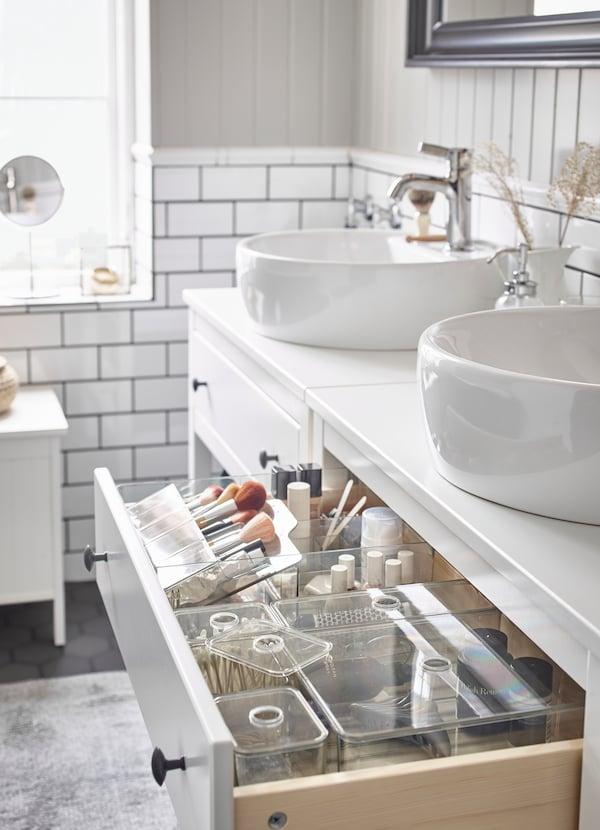 Valoisa kylpyhuone, jossa on valkoiset HEMNES-allaskaapit. Toisen allaskaapin laatikko on auki ja siellä näkyy GODMORGON-sarjan säilytystuotteita.