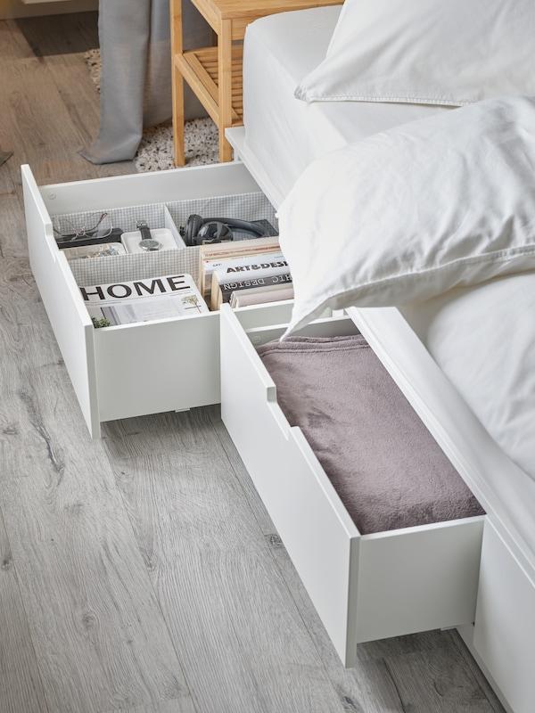 En seng med to åbne sengeskuffer med hvidt sengetøj