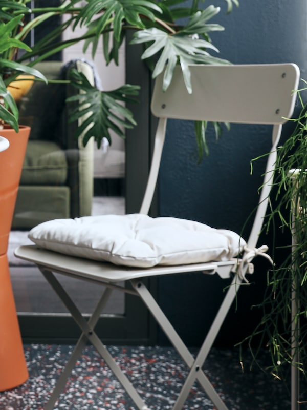 A beige SALTHOLMEN folding chair with a beige KUDDARNA chair cushion sits in the middle of a lot of plants in pots.
