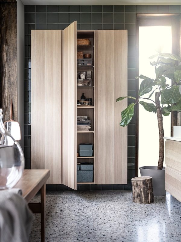 A bathroom with stone floors, a potted ficus, GODMORGON high cabinets in wood, one is open with KUGGIS boxes on the shelves.