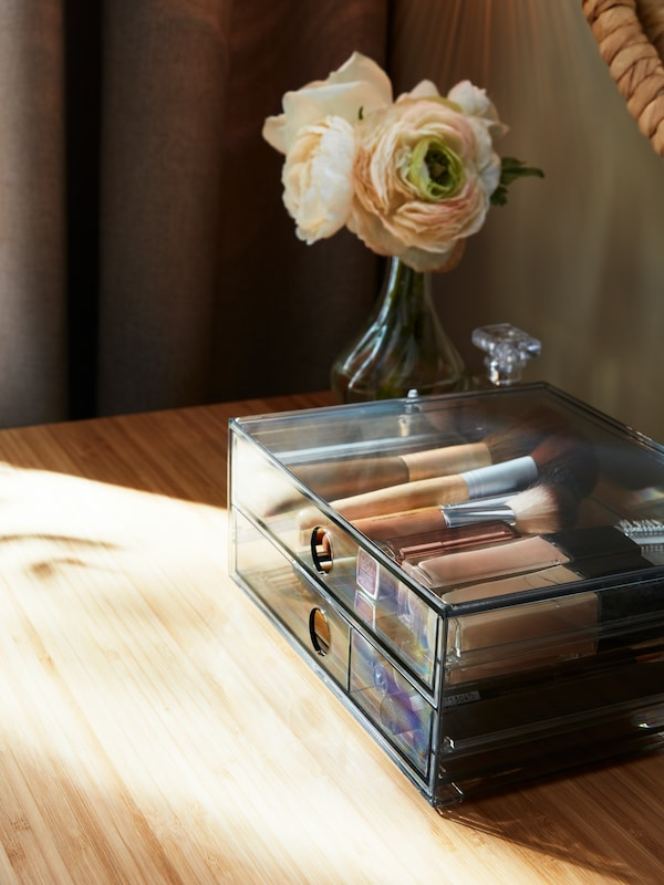 On a wooden surface, a colorless GODMORGON box with make-up inside. Beside a small vase with flowers.
