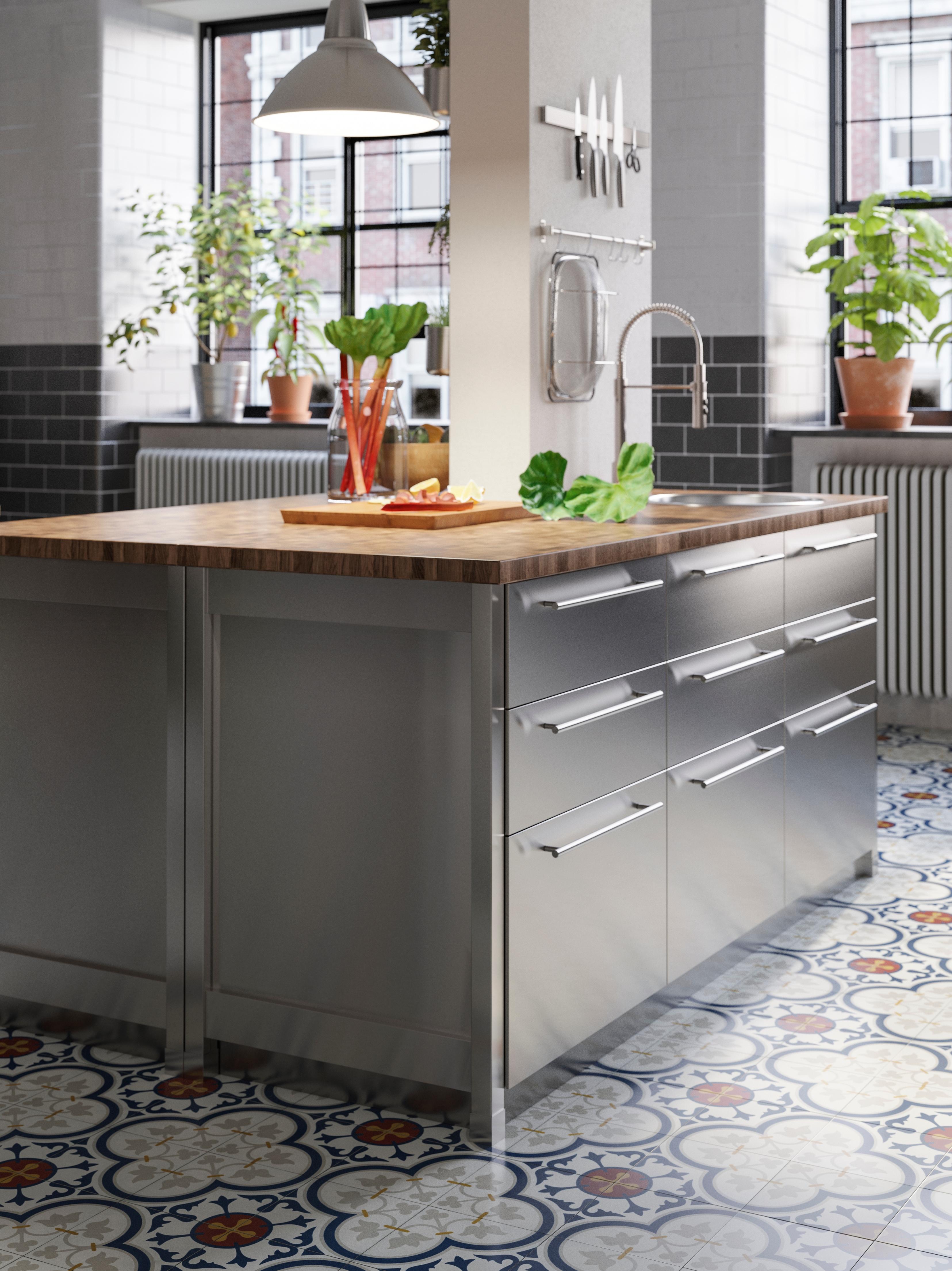 En köksö med SKOGSÅ bänkskiva i ek/faner på bänkskåp med lådfronter i rostfritt stål i ett kök med klinkergolv.